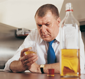 Man looking at glass of alcohol with open bottle of alcohol on table.