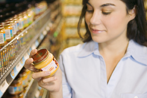 Woman reading label of organic product in grocery store.
