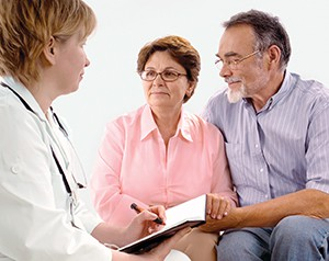 Man and woman consulting with doctor.